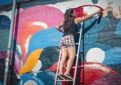 Malarka na drabinie maluje ścianę